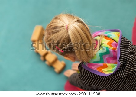 young blond girl is playing with a wooden toy - stock photo