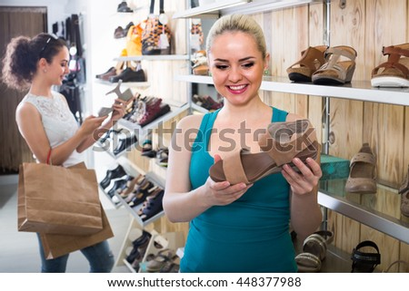 Young blond girl showing a chosen pair of shoes while her friend still choosing - stock photo