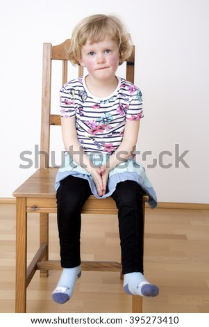 Young blond girl while sitting