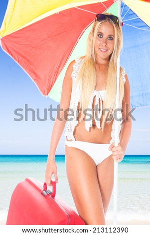 young blond girl with a red suitcase and a colorful sunshade at a beautiful beach with a turquoise sea