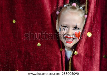 Young Blond Girl with Face Painted in Clown Make Up Smiling and Peeking Out Through Opening in Red Stage Curtains - stock photo