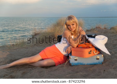 Young blond girl with her luggage sitting nicely on the sand on the beach. She came to the warm country to relax. Light of the sun at sunset.