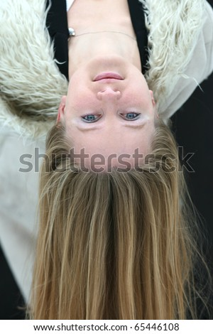 Young blond girl with long hair upside-down