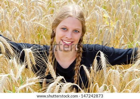 Young, blond girl with pigtails in a wheat field