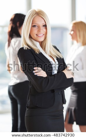 Young blond hair businesswoman standing in front of her associates.