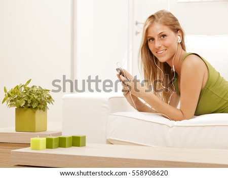 young blond hair girl relax listen to music on sofa