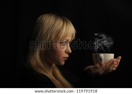 young blond hair woman with coffee  on a dark background. - stock photo