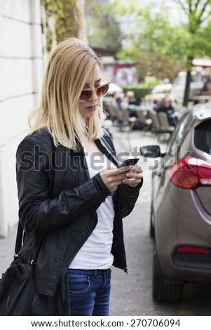 Young blond haired woman with sunglasses standing on the street and typing message on her smart phone. People sitting in the street cafe in the background. - stock photo