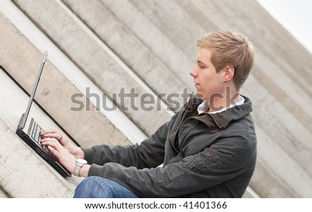Young blond handsome smiling guy sitting outdoors with laptop computer