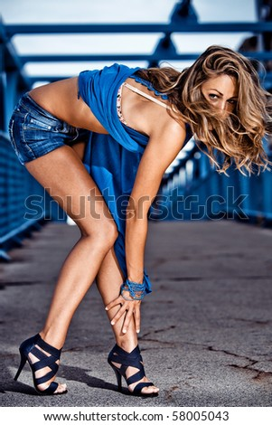 young blond in jeans shorts posing, outdoor shot - stock photo