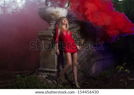 Young blond in short red dress is enveloped by the red smoke