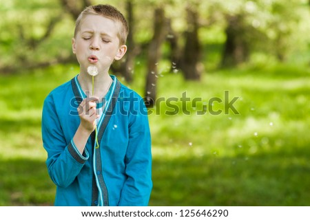 Young blond kid in the meadow blowing wishes on dandelion seed - stock photo