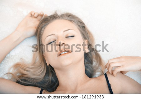 Young blond lady in black lingerie laying on a bed