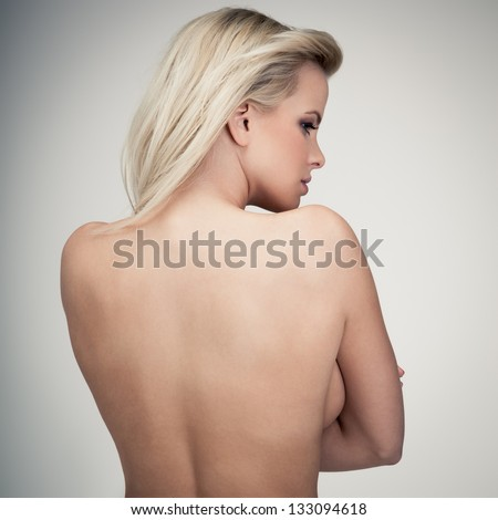 Young blond lady with a beautiful hair on gray background - stock photo