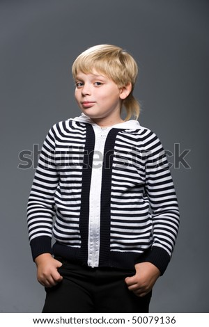 young blond man in a striped sweater with a gray background
