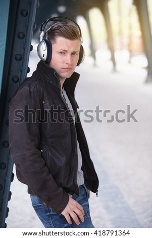 young blond man standing with headphones in the street - stock photo