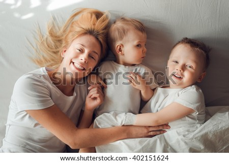 Young blond mother playing with her two sons in bed in the morning - stock photo