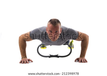 Young blond muscular man exercising on the floor with Pilates ring isolated on white - stock photo