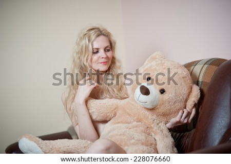 Young blond sensual woman sitting on sofa relaxing with a huge teddy bear. Beautiful girl with comfortable clothes relaxing on the couch with a toy. Attractive blonde in cozy scenery indoor