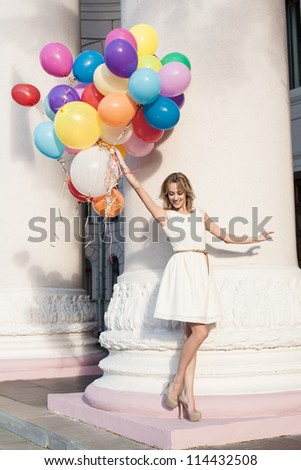 Young blond sensual woman with colorful latex balloons keeping her dress, urban scene, outdoors - stock photo