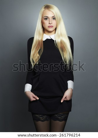 Young blond sexy woman.Beautiful Girl in black short dress.schoolgirl  - stock photo