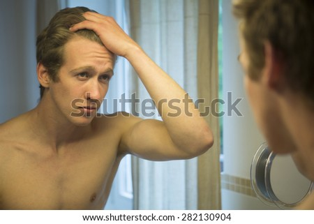 young blond shirtless man looking in the mirror in bathroom - stock photo