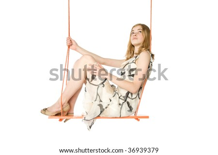 Young blond sitting on a swing, white background - stock photo