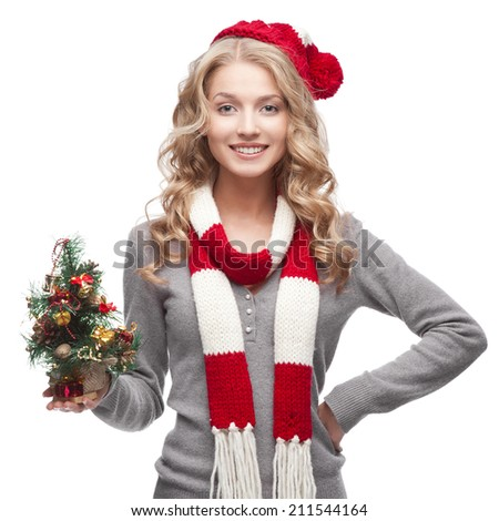 young blond smiling casual woman in red scarf and hat holding christmas tree - stock photo