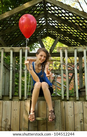 Young blond smiling girl holding a red balloon and doing victory sign