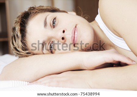 Young blond smiling woman with short hair lying in bed