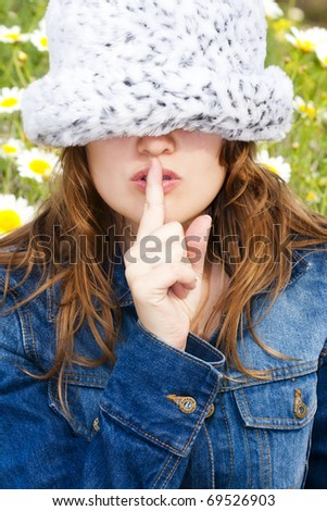 Young blond with her finger on her mouth - stock photo