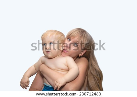 Young blond woman and child smiles - mother and son - stock photo