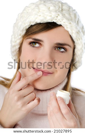 Young blond woman applying lip creme close up - stock photo