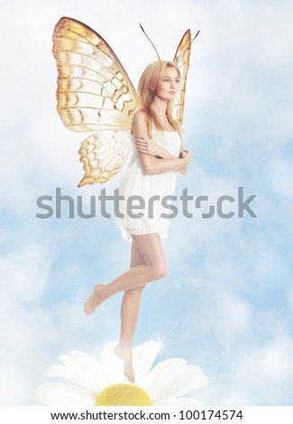 Young blond woman as butterfly on spring daisy - stock photo
