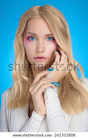 Young Blond woman.Beautiful girl model with make-up.Blue Background - stock photo