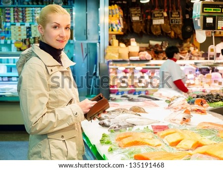 Young blond woman buying fish on market - stock photo