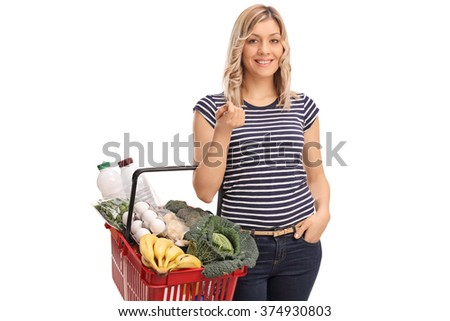 Young blond woman carrying a shopping basket full of groceries isolated on white background