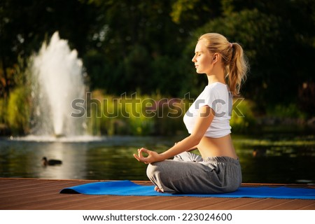 Young blond woman doing yoga and maditating. Sitting in lotus pose with a beautiful green scenery of park on background - stock photo