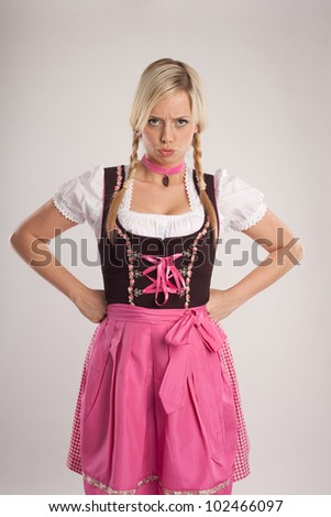 young blond woman dressed with dirndl for oktoberfest is disappointed/young blond angry woman with dirndl costume/woman with dirndl is angry