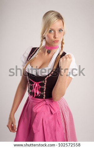 young blond woman dressed with dirndl for oktoberfest warns someone with her fist
