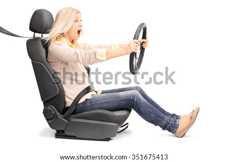 Young blond woman driving very fast seated on a car seat fastened with seatbelt isolated on white background