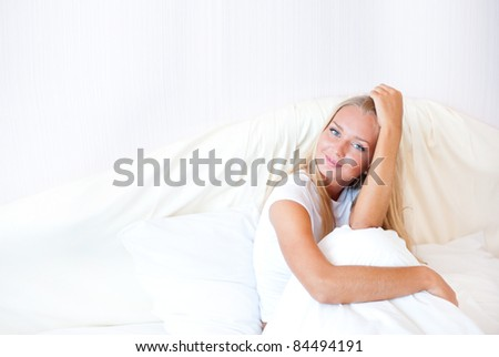 Young blond woman enjoying a sunny morning in bed. Horizontal Shot - stock photo