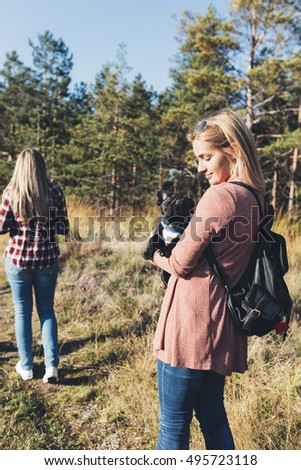 Young blond woman enjoying outdoors with beautiful black French bulldog. Sunny day. Mountain nature.