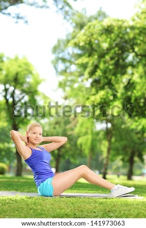 Young blond woman exercising on a mat in a park