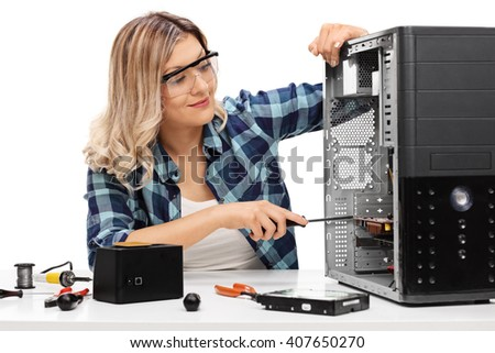 Young blond woman fixing a desktop computer seated at a table isolated on white background