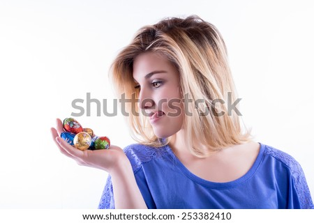 Young blond woman has an appetite for chocolate Easter eggs - stock photo