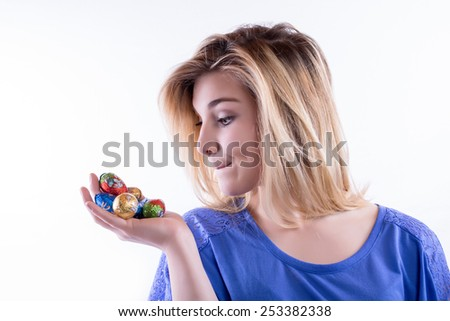 Young blond woman has an appetite for chocolate Easter eggs, but... theres a question - stock photo