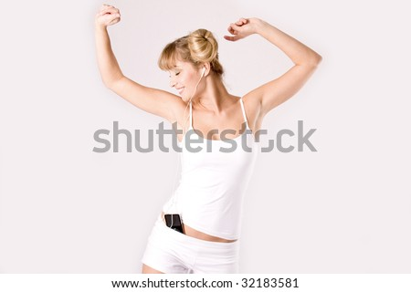 young blond woman hears music with a mp3 player and dances - stock photo