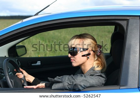 young blond woman in a blue car in sun-glasses with hands free headset - stock photo