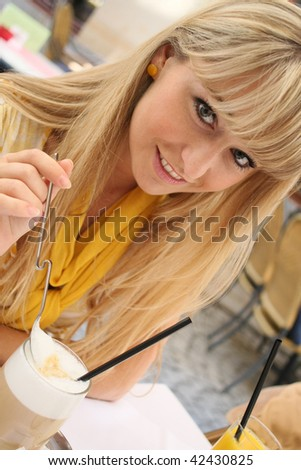 young blond woman in a cafe with a glass of latte macchiato
